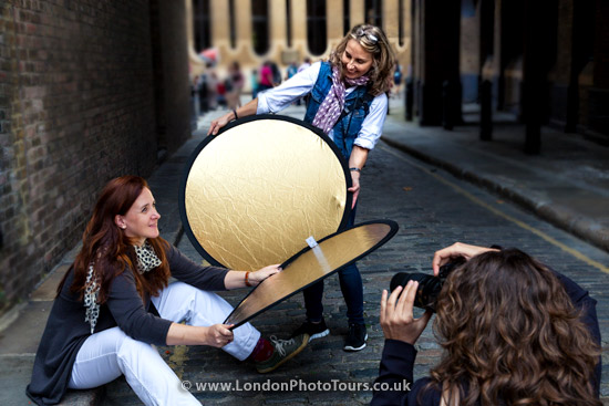 three women on an outdoor portrait photography workshop sitting and using reflectors and posing for a photography