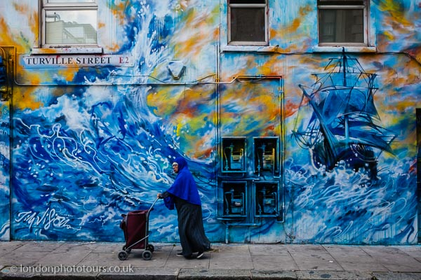 Photo of Woman with shopping trolley walking in front of Shoreditch Street Art